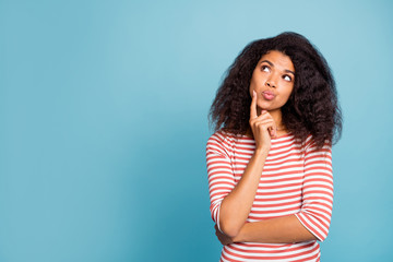 Photo of pretty dark skin lady looking empty space wondered think over philosophy questions wear casual striped sweater isolated pastel blue color background