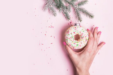 Wall Mural - Female hand hangs Christmas bauble decoration made of donut on pink background. Christmas creative concept
