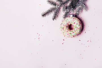 Wall Mural - Christmas creative background. Christmas ball made of decorated donut hanging on Christmas tree branch