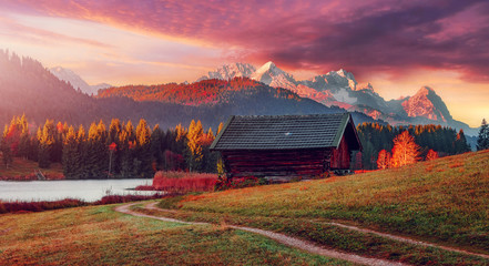 Fotomurales - impressive sunset at Alps. Wonderful Picturesque landscape with colorful dramatic sky over the mountain valley with fairy lake and Zugspitze on background. Tipical Alpine hut on meadow under sunlit