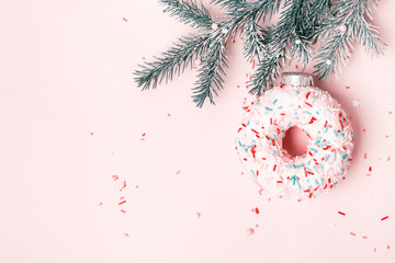 Wall Mural - Christmas toy glazed donut with sugar sprinkling hanging on Christmas tree branch. Pink pastel background