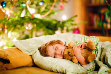 Little cute blond boy sleeping under Christmas tree and dreaming of Santa at home, indoors. Traditional Christian festival. Happy kid child waiting for gifts on xmas. Cozy soft light