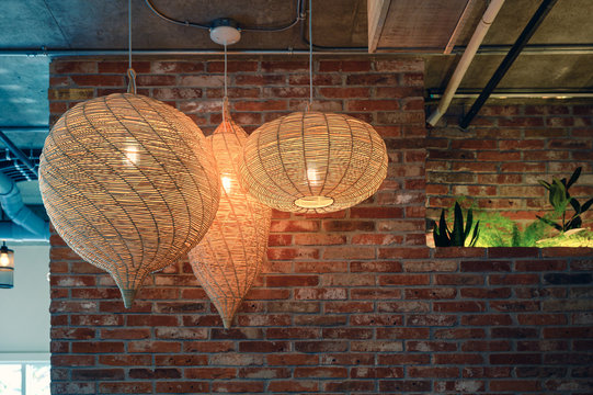 Wooden weave lamp hanging on ceiling and brick wall