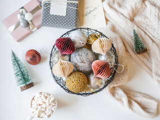 Metal wicker basket with various gold and silver Christmas balls, hot drink in mug and Christmas decorate on white background.