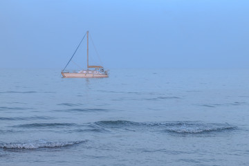 White sailboat in the sea. Blue hour. Calm and tranquility.