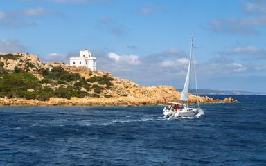 White yacht struggling with the wind near rocky coast of La Maddalena, Sardinia, Italy.
