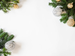 Flat lay creative Christmas frame with fir branches and Christmas balls on white background. Top view.