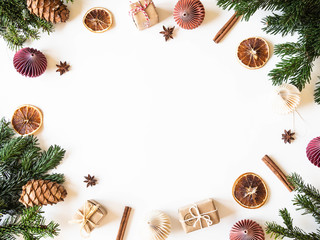 Flat lay creative Christmas vibrant frame with fir branches, Christmas decorations and spices on white background. Top view