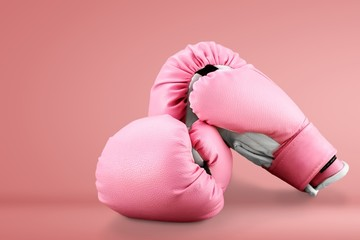 Pink boxing gloves on wooden desk