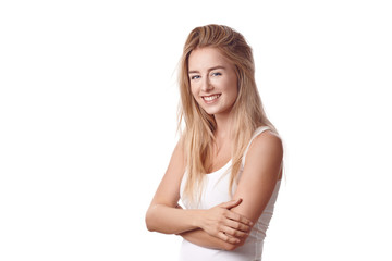 Beautiful blond young woman standing in white shirt with arms folded against white background, smiling and looking at camera. Half-turn half-length portrait