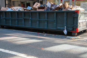 Long overflowing metal dumpster on a asphalt street in front of businesses