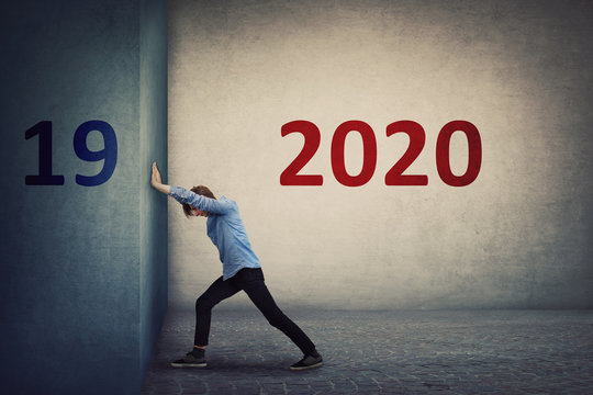 Conceptual scene as a confident person pushing the 2019 old wall to make space for the coming new 2020 year. Determined guy announcing a new start, ready for change and challenges.