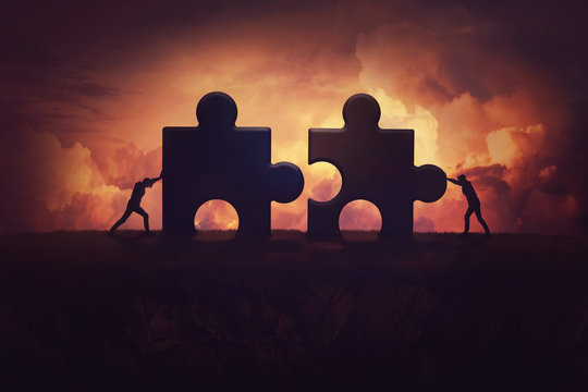 Two determined businessman pushing big jigsaw puzzle pieces to unite and complete the purpose. Business teamwork concept, achieving success together by joining forces. Group cooperation process.