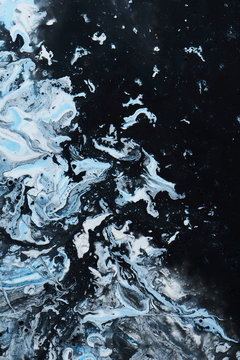 Abstract liquid paint exoplanet background. White snow ice floes in the ocean sea of black oil. Macro mold or fungus backdrop