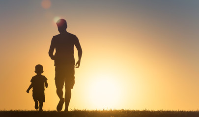 Father and child, son playing running in the park at sunset.