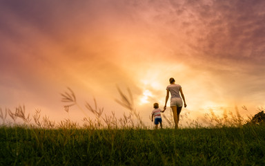 Mother child holding hands walking in the park at sunset.