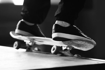 A black-white image of a man's feet, doing a slide on a skateboard on a ramp.