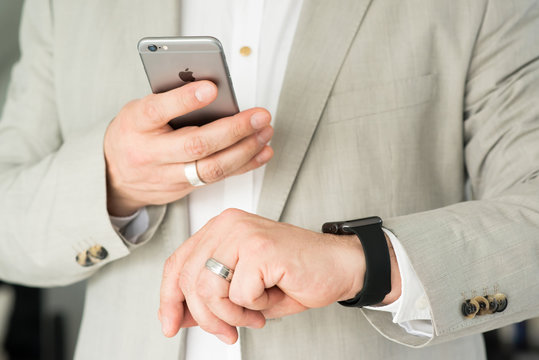 Businessman using the Apple Watch and an Apple iPhone 6