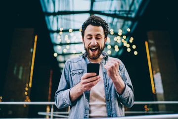 Emotional caucasian hipster guy excited with result of match victory watching video online on smartphone and 4G connection, happy millennial male overjoyed with get new free app for mobile phone .