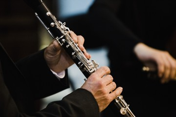 Clarinet player holding a metal transverse flute in his hands.