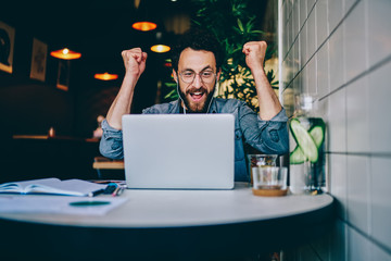 Overjoyed hipster guy in earphones cheers for team watching match on laptop computer during free time in cafe interior, amazed emotional male freelancer celebrating achievement and completing project.