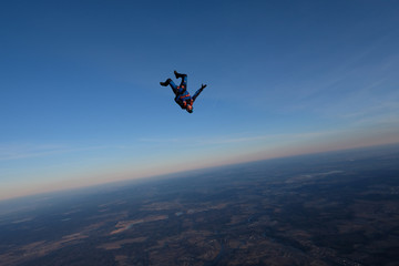 Skydiving. A solo skydiver is in the sunset sky.