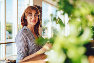 Portrait of gladden hipster girl in optical eyewear for provide eyes protection smiling at camera during spare time in public cafeteria, happy cheerful woman with red hair enjoying leisure indoors