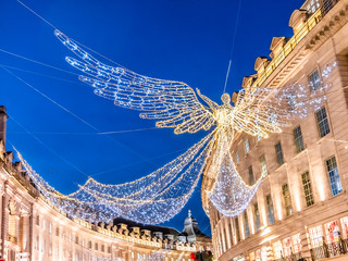 Big angel shape made by lights outdoors above Regents street in London in Christmas winter time