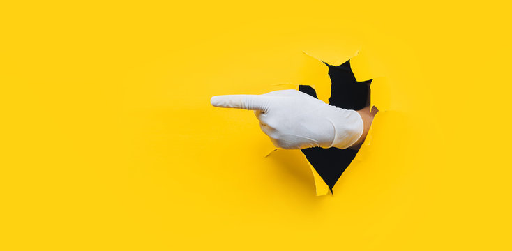 The forefinger points in white medical glove to the left side. Yellow paper background with torn hole. Place for advertising. Copy space.
