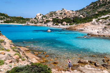 Sardinia, holidays, beautiful beaches of the archipelago of the Maddalena with crystal clear azure water surrounded by rocky mountains. Tourists taking photos and relaxing. Italy, beaches in Sardinia.