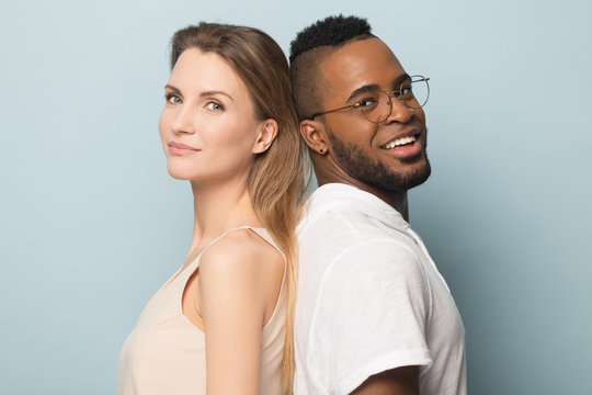 Smiling African American man and woman standing back to back