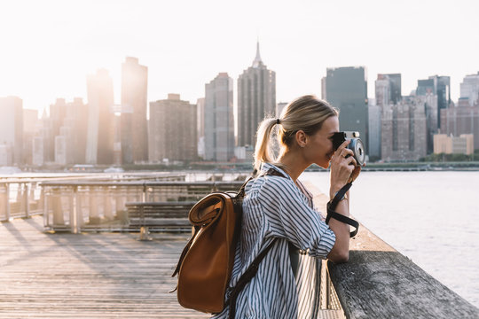 Side view of skilled hipster girl with instant camera clicking picture of city landscape standing at urban setting with Manhattan view, positive female tourist with backpack enjoying getaway