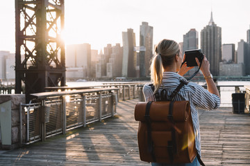 Back view of stylish female tourist with traveling backpack standing on American urban setting and clicking pictures of Manhattan landmark using retro instant camera, concept of photography hobby Fotomurales