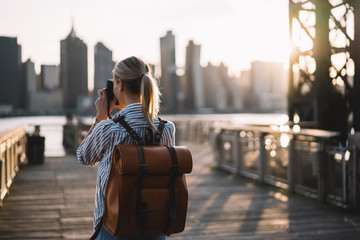Back view of skilled amateur photographer taking pictures of American city enjoying summer trip to USA, female tourist with trendy rucksack testing modern technology for making view photos