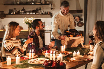 Photo of caucasian excited people having Christmas dinner with turkey