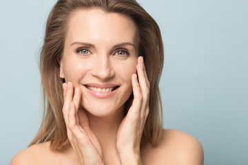 Head shot portrait smiling woman touching perfect smooth face skin