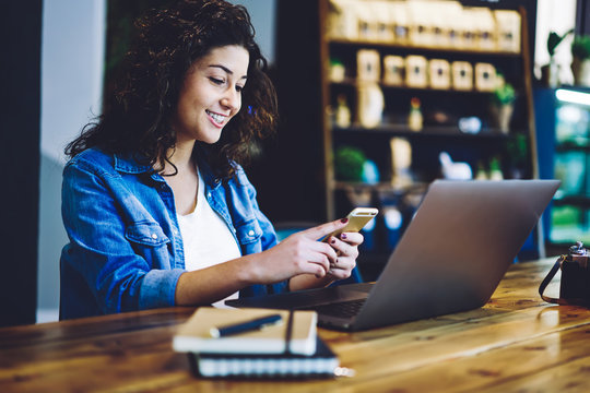 Cheerful hipster girl dressed in casual wear reading received email from friend in social networks while working with presentation for course work, happy woman messaging via application on cellular