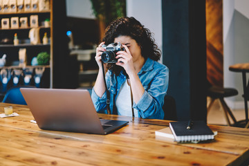 Young female amateur in casual wear taking pictures of laptop screen via old fashioned equipment during spending leisure time for training photographing skills, skilled journalist making images