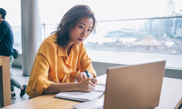 Asian female writing and looking at screen display at workplace