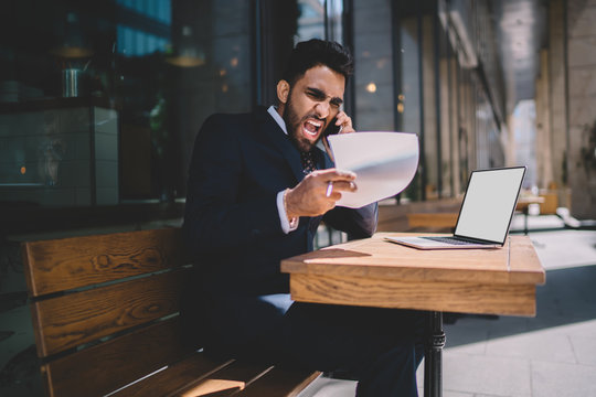 Angry turkish man in formal wear feeling rage while checking data from accounting report calling to employee and shouting for bad work while sitting outdoors with netbook with blank screen area