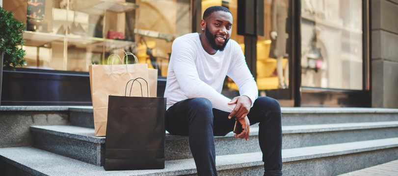 Portrait of afro american male hipster resting after shopping on weekend sitting on stairs with paper bags, smiling dark skinned guy looking at camera enjoying recreation after buying purchases
