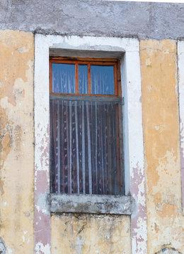 Window with Sheer Curtains in a Building with Chipped Gold Paint over Stucco