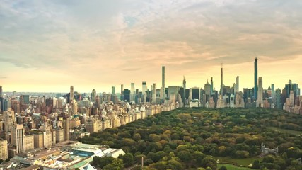 Fototapete - Aerial drone footage of New York midtown skyline at sunset viewed from above Central Park, with slow forward camera rotation