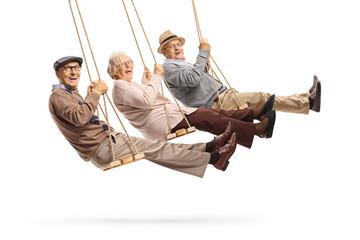 Happy senior people swinging on swings