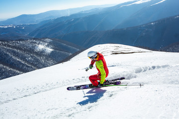 Fototapete - A man is skiing down the hill on the steep slope in Carpathians. Ukraine. High mountain area.