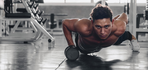 caucasian man having workout for bodybuilding by pushing up with holding dumbbells in one hand in fitness center