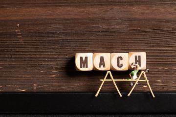 """Kleine Malerfigur schreibt """"MACH"""" auf Würfel"""