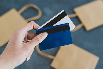 hand holding payment cards in front of the camera with shopping bags bokeh in the background