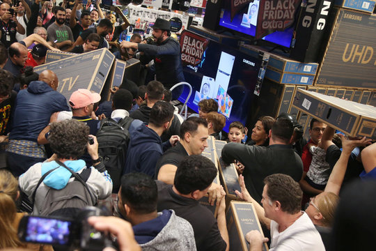 Shoppers reach for television sets as they compete to purchase retail items on Black Friday at a store in Sao Paulo