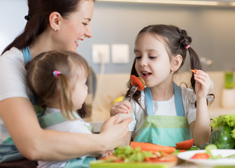 Child tasting food during cooking with their mother and sister